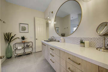 The private, en suite bathroom features a tile shower and double vanity sinks.