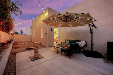 The back patio features an oversized solar umbrella, a patio couch with seating for five and plenty of games for the whole group to enjoy.
