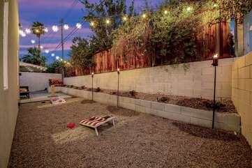 Challenge your buddy to a game of bean bag toss under the lit up patio lights.