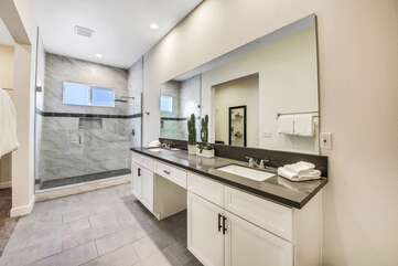 The private, en suite bathroom features a tile shower and two vanity sinks.