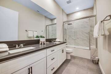 The hallway bathroom is located between bedroom 2 and 3 and features a double vanity sink and a combo shower/tub.