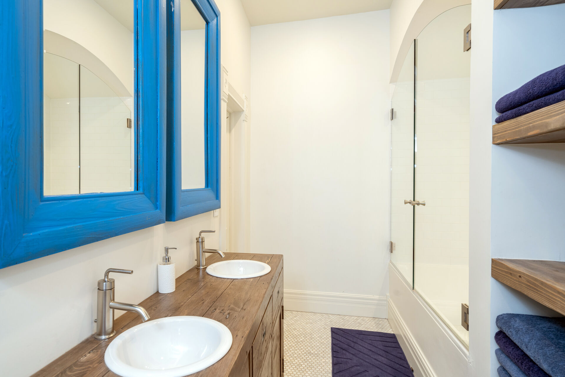 Blue framed mirrors above a pair of sinks in the bathroom.