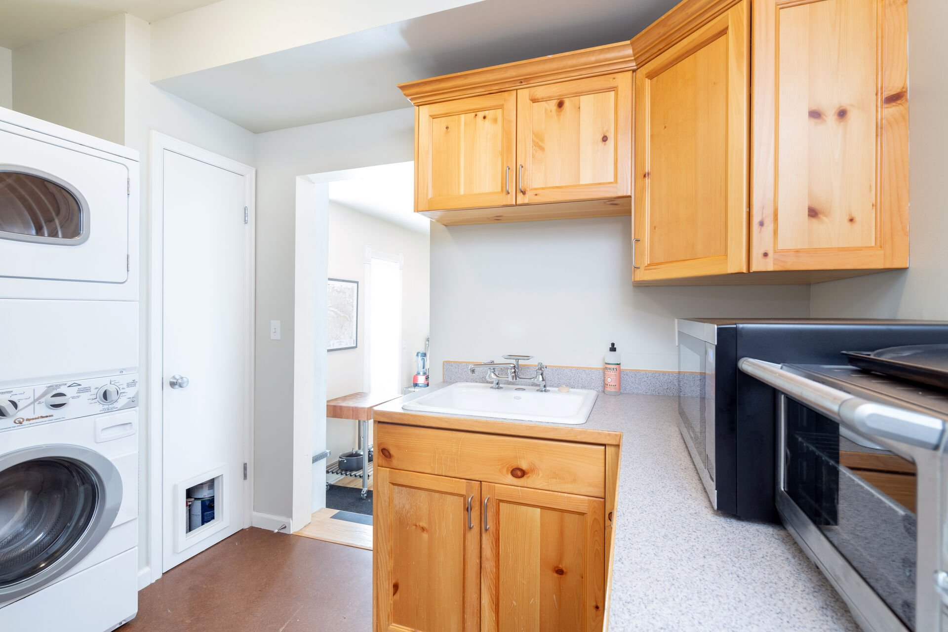 Laundry room with washer, dryer, sink, microwave, and toaster oven.