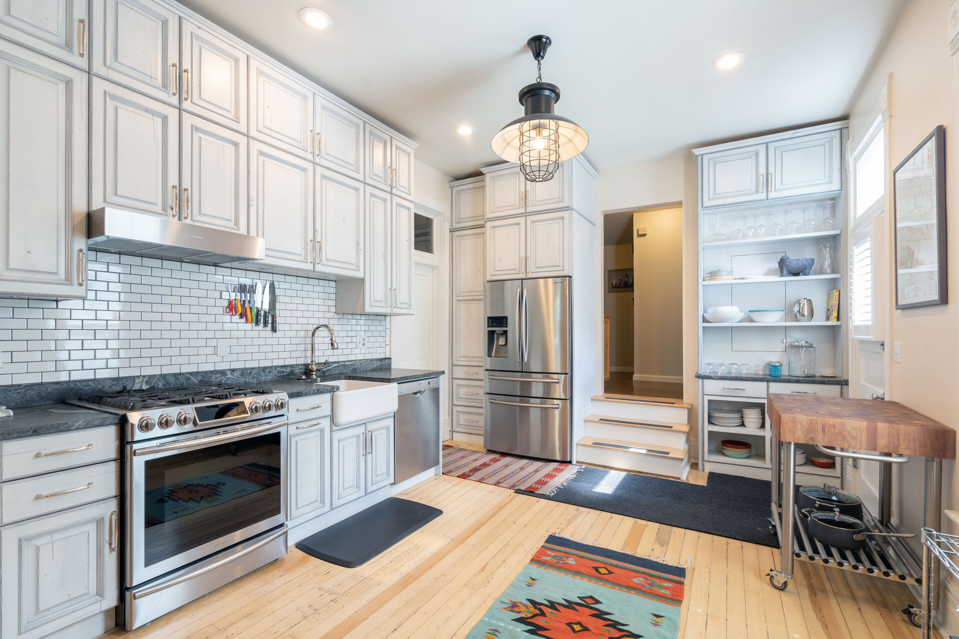 The kitchen of this holiday home in Telluride, with stainless steel appliances and a mobile kitchen counter table.