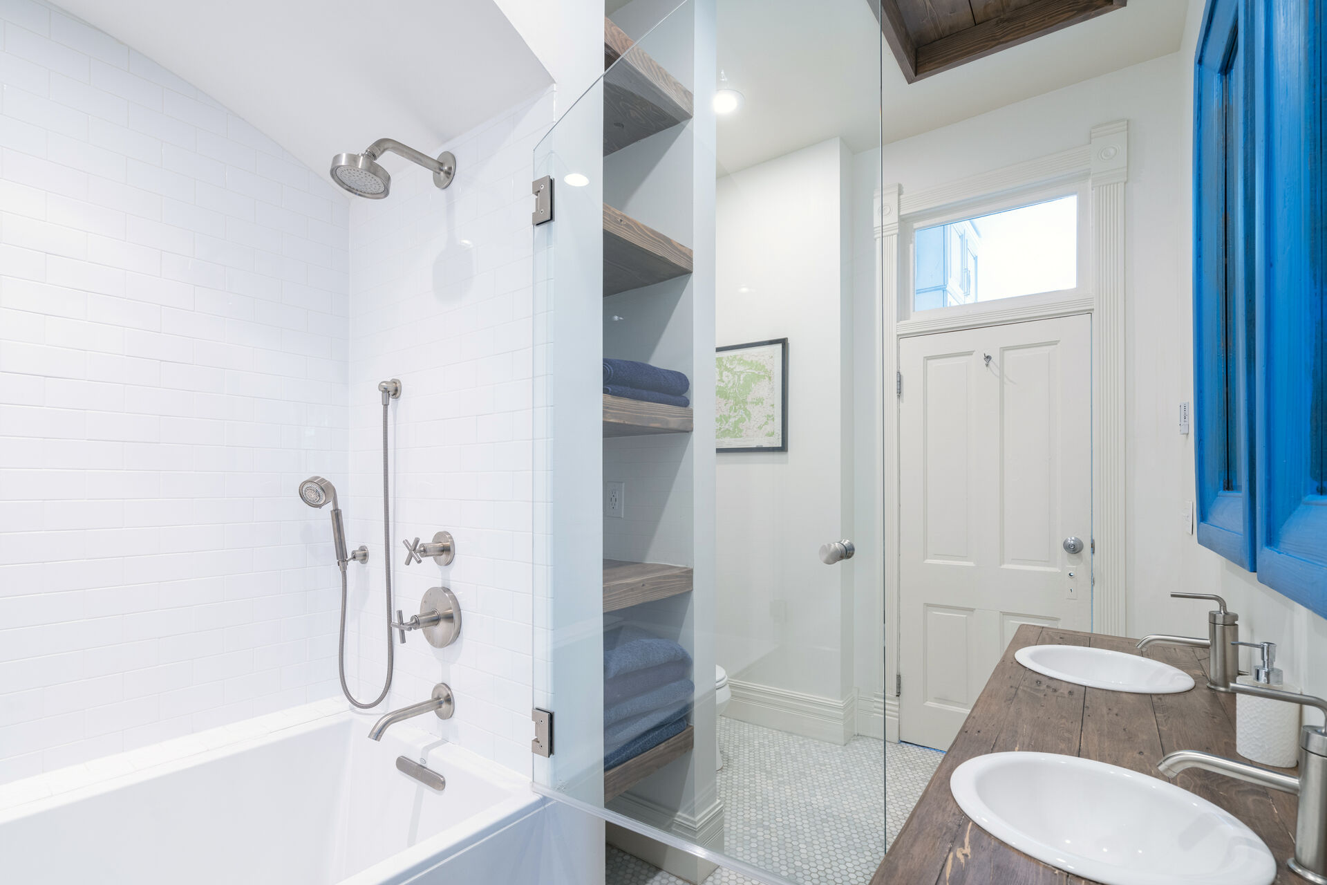 Bathroom with glass-doored shower, double vanity sinks, and shelves built into the walls.
