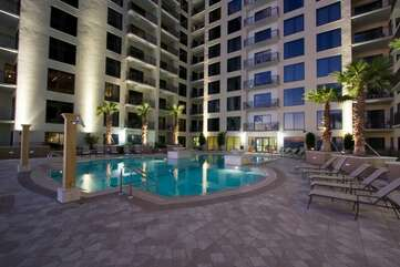 Night time of the pool located on the 4th floor, with outdoor showers and hot tubs