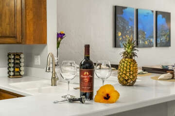 Two Wine Glasses, a Wine Bottle, and a Pineapple on the Kitchen Counter