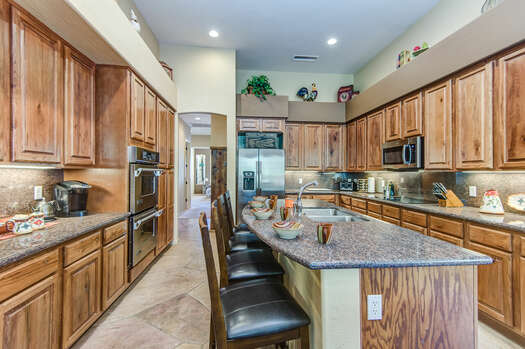 Large Fully Equipped Kitchen with Expansive Granite Countertops and Lovely Wood Cabinetry