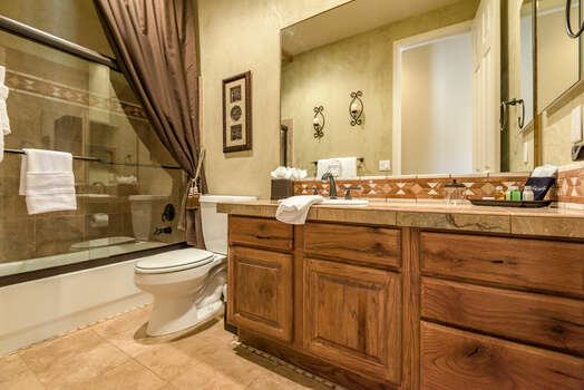 Full Shared Bathroom with a Stone Counter Sink and a Tub/Shower Combo