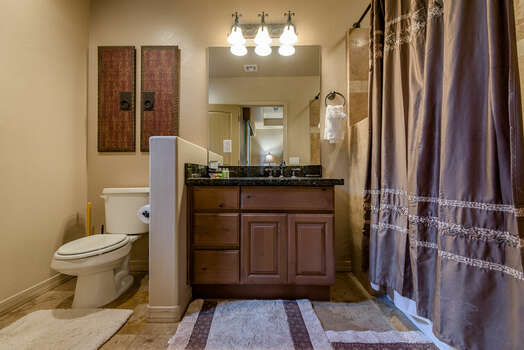 Full Bathroom with a Granite Counter Sink and a Tub/Shower Combo