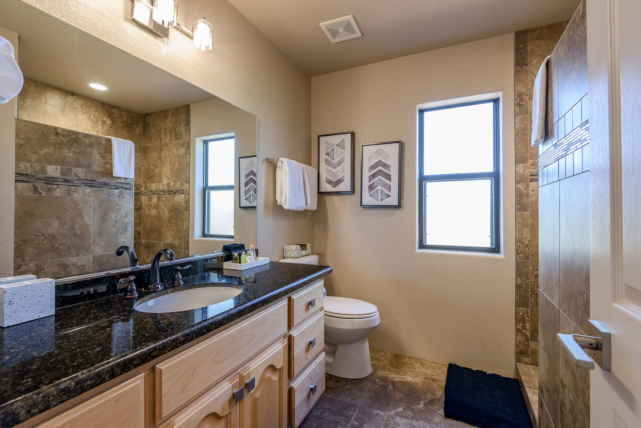 Full Shared Bath with Stone Counter Sink and Tile Shower
