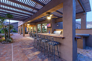 The covered outdoor bar with built-in gas grill, beer fridge and TV will be a favorite place to celebrate with family and friends.