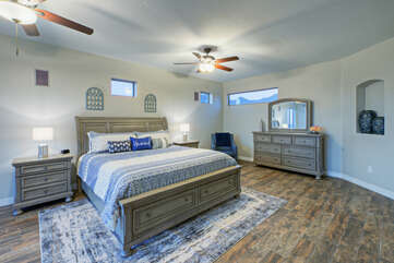 The primary bedroom is on the second floor and has a trey ceiling, 2 ceiling fans, a king bed, walk-in closet and a desk for remote work.