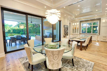 Dining with kitchen providing additional seating.  sliding door to summer kitchen and pool.