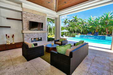 Outdoor living area overlooking the pool - with fireplace and TV. Open to outdoor dining and summer kitchen.