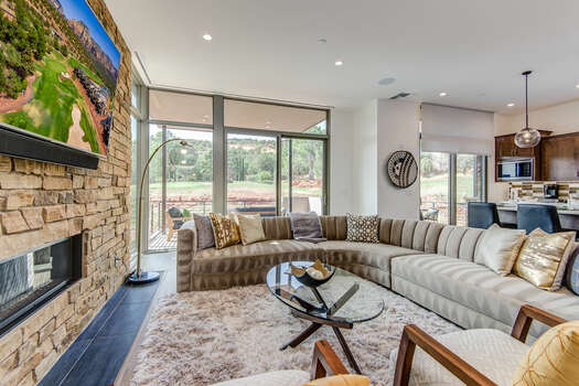 Living Room with a Large Sectional Sofa and  Patio Access with Golf Course and Mountain Views