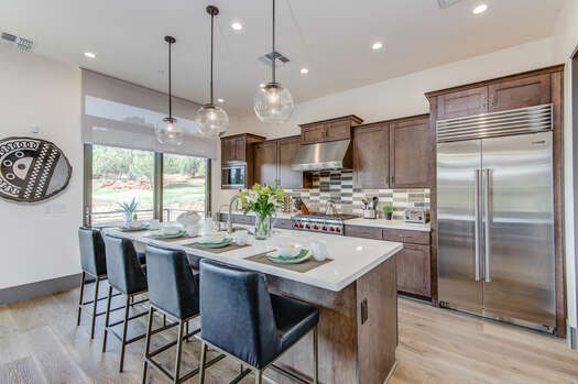 Spacious Gourmet Kitchen with Stone Counters and High-end Stainless Steel Appliances, Including a Wolf Gas Range and a SubZero Refrigerator