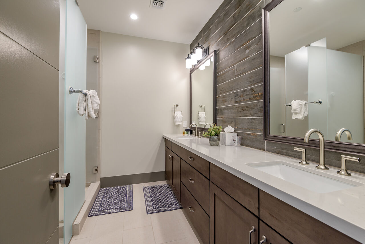 Full Shared Bath with Dual Stone Counter Sinks and a Shower