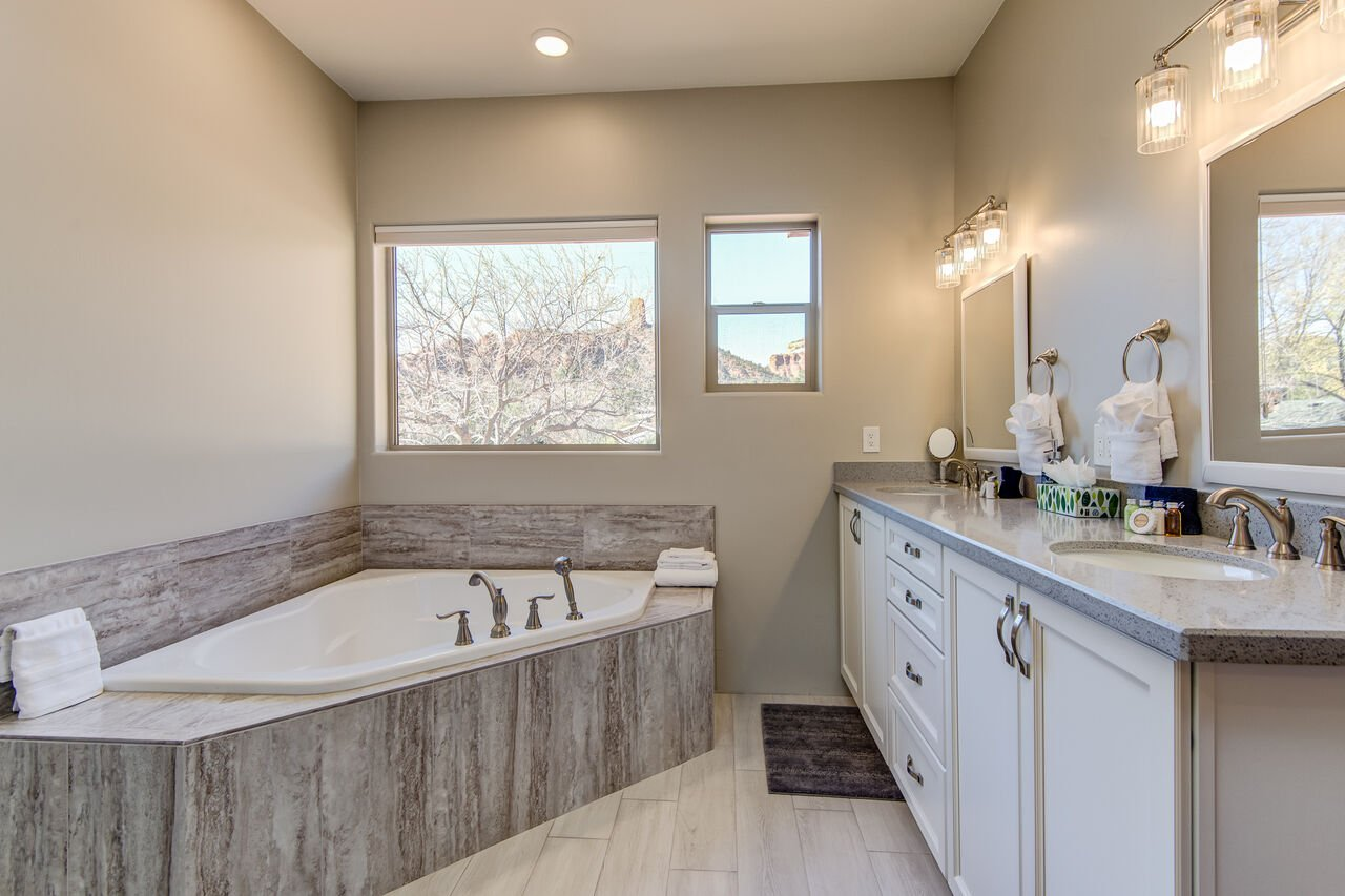 En Suite Master Bath with Dual Stone Counter Sinks and a Soaking Tub