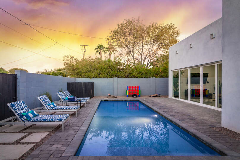 Large pool with seating and lawn games.
