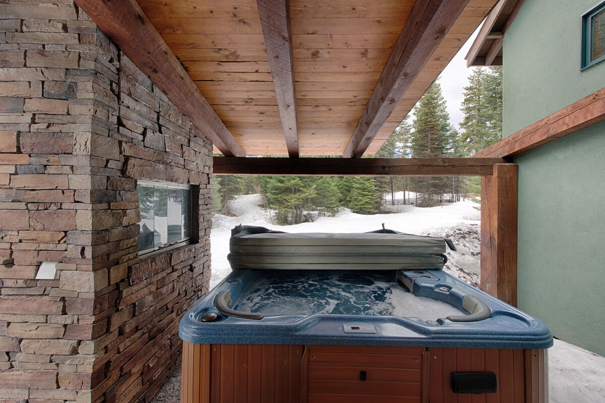 Hot tub has forest view.