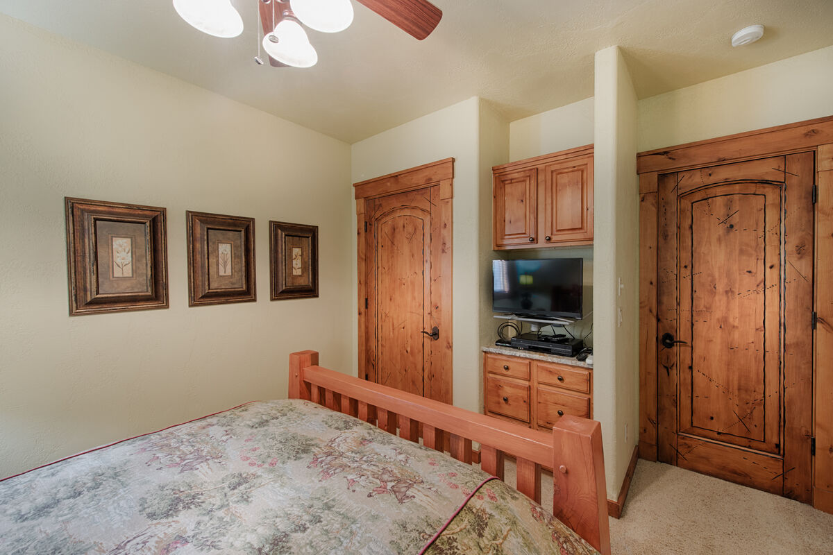 Guest bedroom has television.