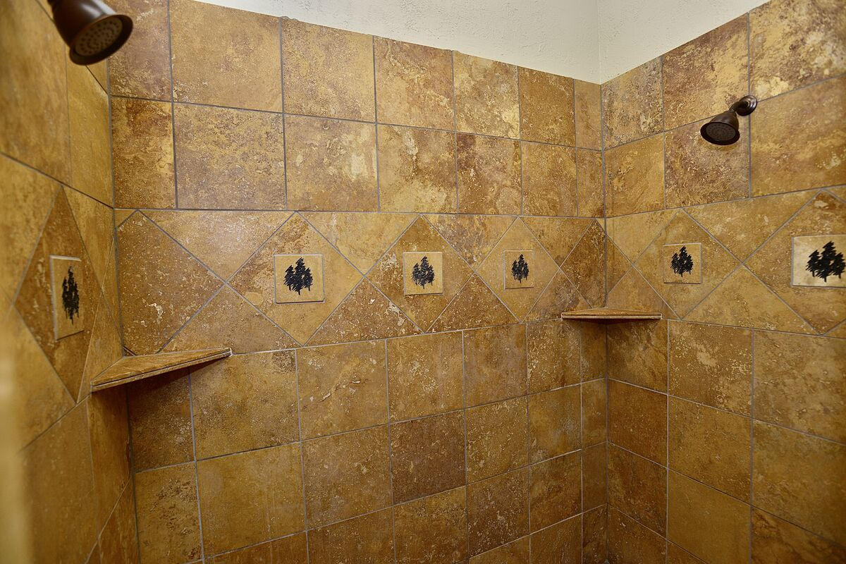 large tiled shower with dual shower heads in the master bath