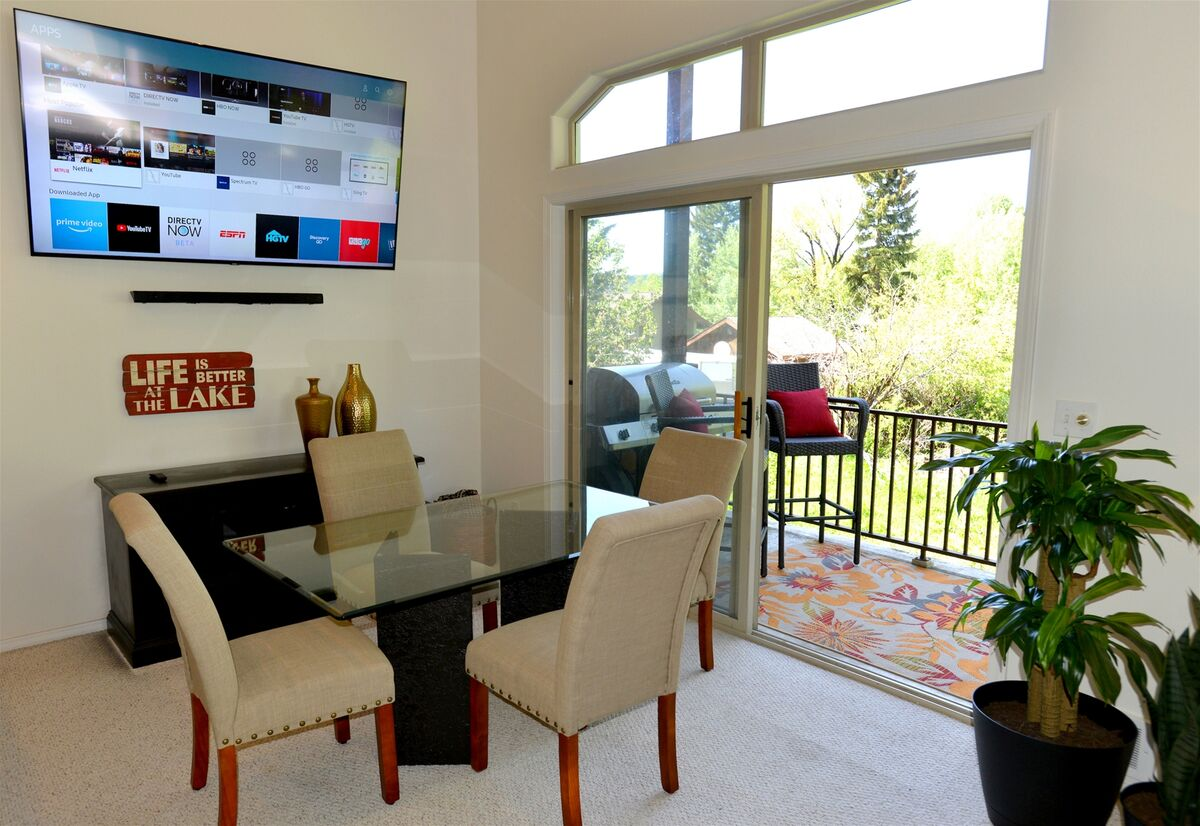 Dining area has big screen TV and balcony access with lake view.
