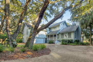 Front view with beautiful live oaks