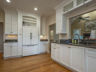 Fully equipped updated kitchen with white appliances and granite counter tops.