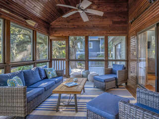 Screened porch off dining room and kitchen with ample seating for relaxing.