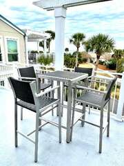 4 high top chairs for dining or playing games. Also a view for watching the dolphins and pelicans.