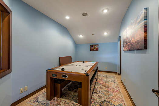 Adjacent Game Room with an Air Hockey Table and an Electric Dart Board
