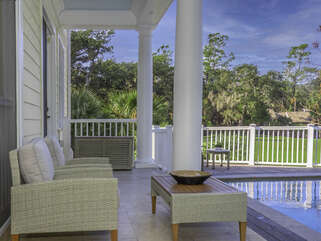 Back deck with a pool and view of golf course.