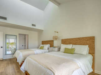 Seagrass woven headboards and plush bedding  make for a comfortable retreat.