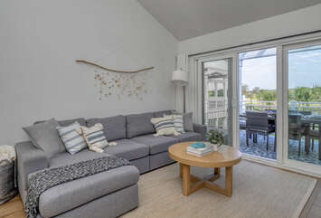 A large grey sectional is the perfect comfort zone landing spot. Large sliders open on to the deck with expansive views of Ocean Winds golf course.