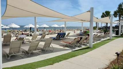 Beach umbrellas and sun sails provide shade to the lounge chairs. Picturesque views of the ocean.