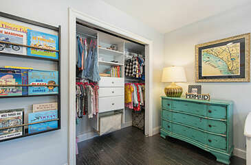 This second bedroom has a closet organizer and a small library of books for the kids.