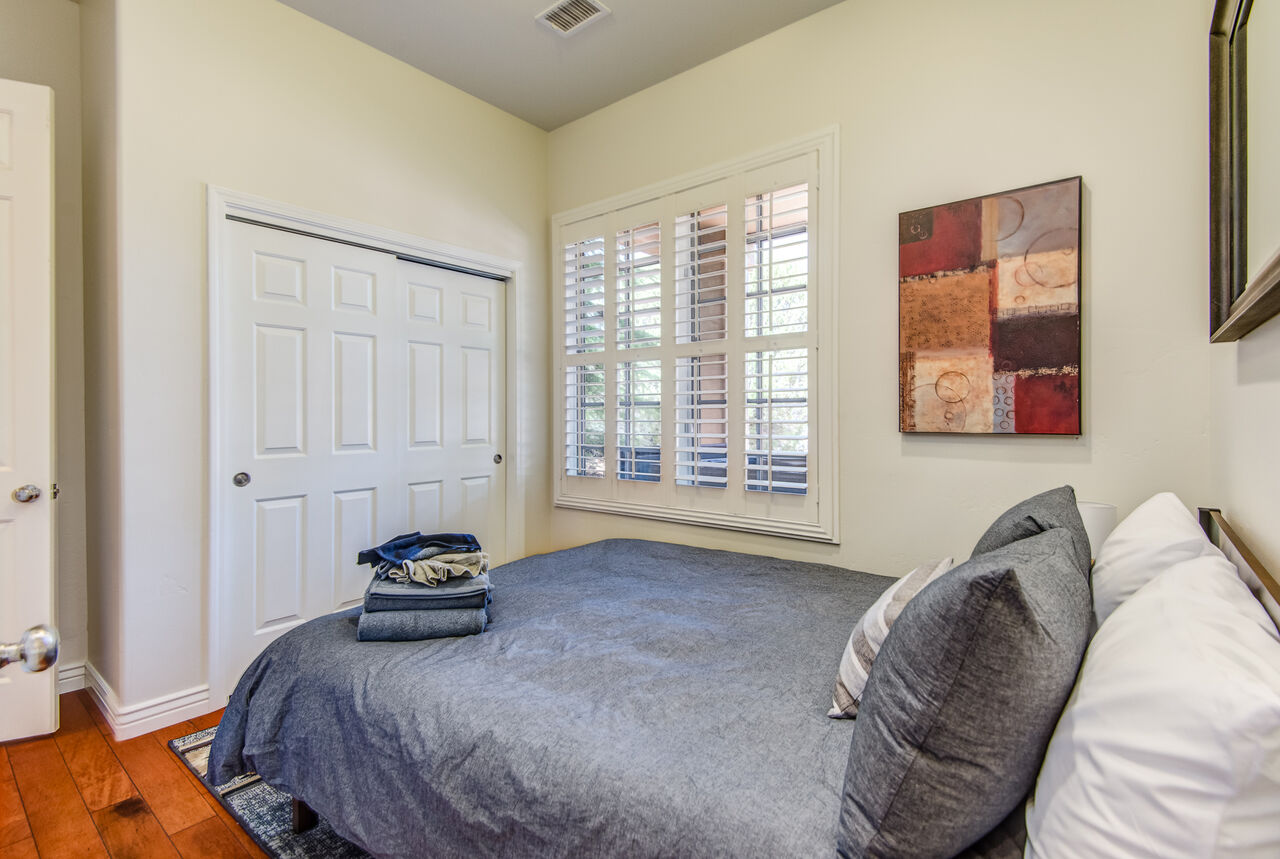 Bedroom 4 with a Queen Bed and Smart TV. Access to a Full Shared Bath