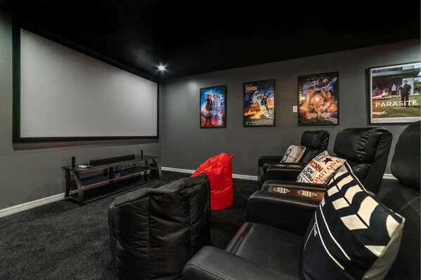 The private theater features theater-style recliners and a projector screen