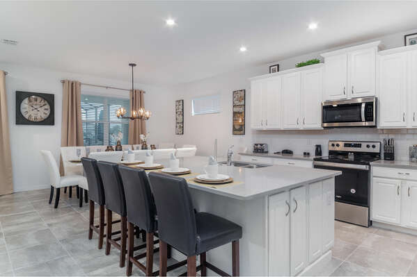 The open kitchen is bright and airy with barstool seating for four