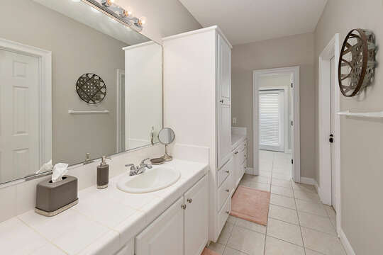 Master Bathroom with double vanity and a large walk-in closet