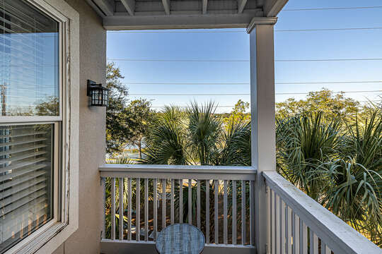 Master Bedroom front balcony with seating overlooking the marsh through beautiful palm trees