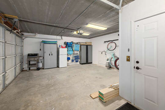 Garage area with a Weber gas grill, chairs, and a beach cart