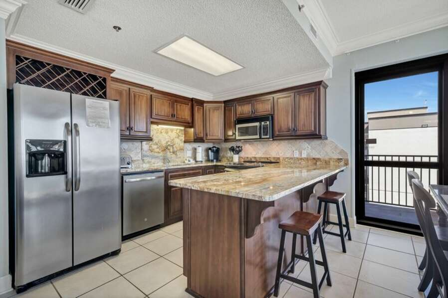 Spacious Fully Equipped Kitchen with Stainless Steel Appliances and Seating at the Breakfast Bar