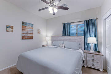 The third bedroom has a king bed and ceiling fan.