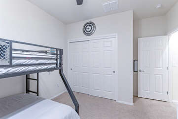 Top twin bed has ladder and rails to enhance safety.