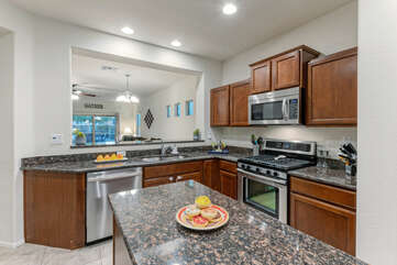 Modern kitchen has stainless steel appliances and is well stocked with culinary tools.
