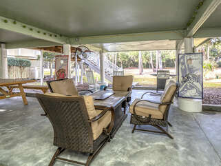 the covered car port has a picnic table, firepit table, gas grill, rockers and corn hole!