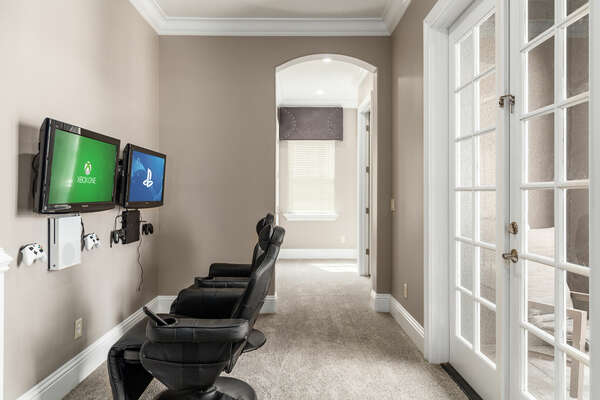 The upstairs hallway now includes a gaming area with comfortable chairs, equipped with Xbox One and a PS4.